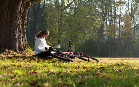 Woman cyclist with read the map sitting on halt  illuminated by the rays of sunlight among the green park photo