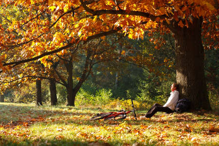 Woman cyclist relaxing in autumn park near the golden old oak tree photo