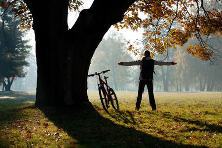 Excited woman cyclist standing in a park with hands outstretched embracing vitality freedom. Outdoor photo