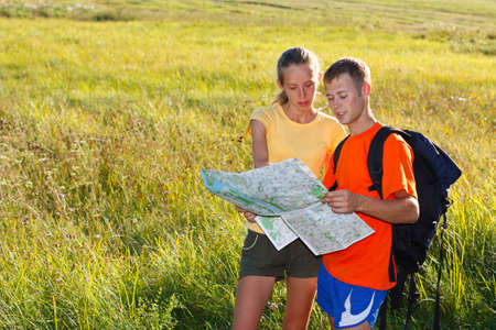 Young couple traveler read the map against a background of green summer nature