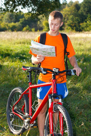 Man cyclist read the map among the green sunligts nature photo