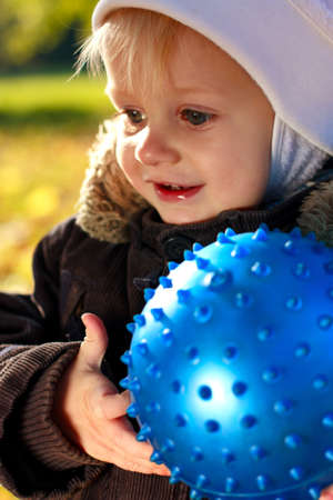 Portrait happy smiling child with blue ball in his hands against a background of green blurred nature photo