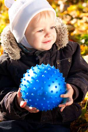 Happy smiling child with blue ball in his hands against a background of autumn sunny nature photo