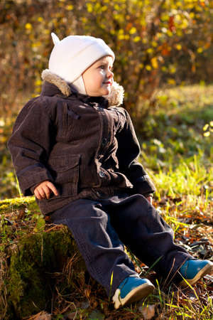 Cute child sitting on a stump against a background of green sunny nature Stock Photo - 12580598