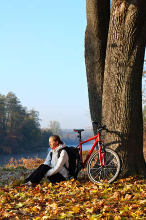 Happy woman cyclist with bike sits among fallen leaves autumn morning in nature illuminated by the rays of the rising sun