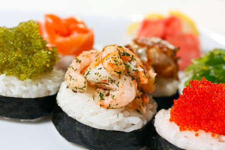 Sushi Canape with eel, shrimp, tobiko caviar, wasabi and salmon close-up photo