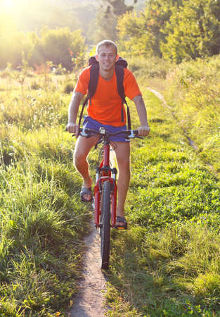 Cyclist riding a bicycle on the road with a backpack behind shoulders against a background of summer solar nature photo