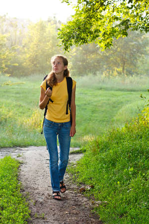 Happy young woman tourist with a backpack walking in summer sunny green nature photo
