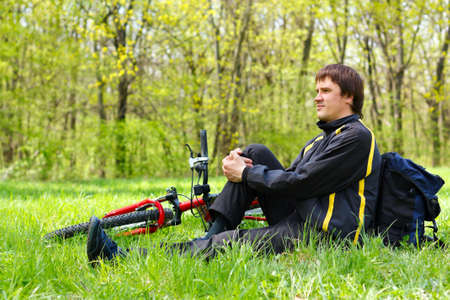 duffel: Happy man cyclist with bike and backpack sitting on green grass against the background of nature in spring on a sunny day