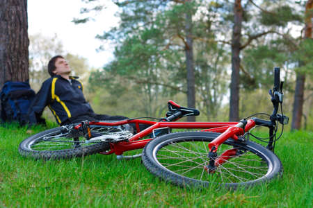 relaxes: Red bike lying on green grass. Cyclist relaxes under the tree in the background against the background of green nature