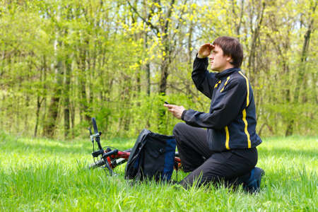 dint: Man cyclist looking for direction of the route by dint of GPS  sitting on green grass against the background of nature in spring on a sunny day