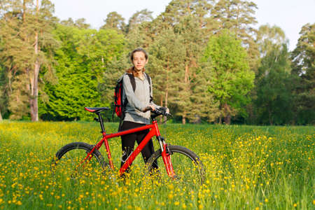 Woman cyclist with bike and backpack against the background of green blooming nature in spring on a sunny day photo