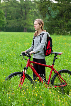 Woman cyclist with bike and backpack against the background of green grass and blooming nature in spring photo