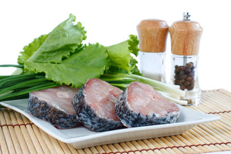 Fillet of fresh raw fish carp on a plate with herbs lettuce, green onions and spices  Isolated on white photo