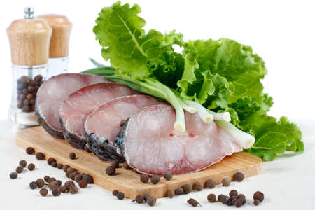 Fillet of fresh raw fish carp on a cutting board with herbs lettuce, green onions and spices  Isolated on white photo