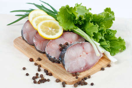 Fillet of fresh raw fish carp on a cutting board with herbs lettuce, green onions, lemon and spicy peppers photo