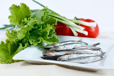 anchovy fish: Anchovy fish on a plate with herbs lettuce, green onions and tomatoes