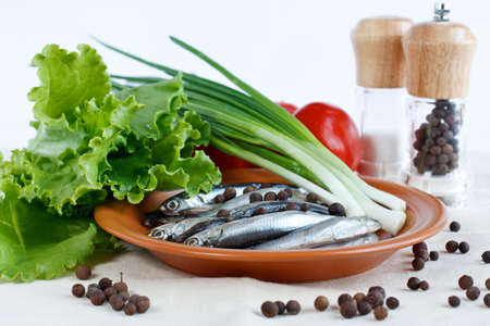 sprat: Anchovy fish on a plate with herbs lettuce, green onions , tomatoes and spicy peppers