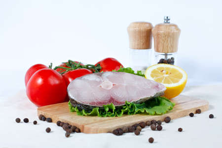 Fillet of fresh raw fish on a cutting board with branch of tomatoes, lettuce, lemon and spicy peppers photo