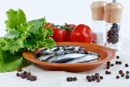 anchovy fish: Anchovy fish on a plate with herbs lettuce, branch of tomatoes and spicy peppers