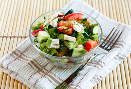 Salad with fresh vegetables and feta cheese in a salad bowl on a fabric napkin Stock Photo - 13818181