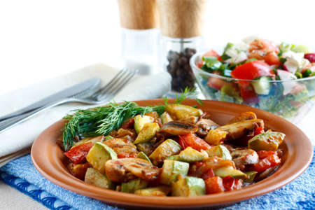 Roasted vegetables on a rustic plate  Salad with fresh vegetables and spices in the background  Isolated on white photo