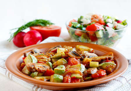 Roasted vegetables on a rustic plate  Salad with fresh vegetables and  salad ingredients in the background photo
