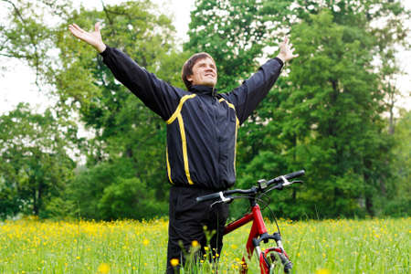 duffel: Excited happy man cyclist among the green nature with hands outstretched embracing vitality freedom  Outdoor