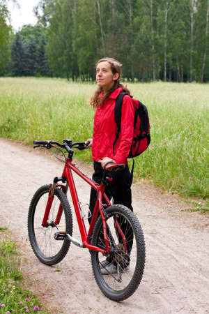 Woman cyclist with bike and backpack in a red tracksuit on a bicycle walk on the green nature