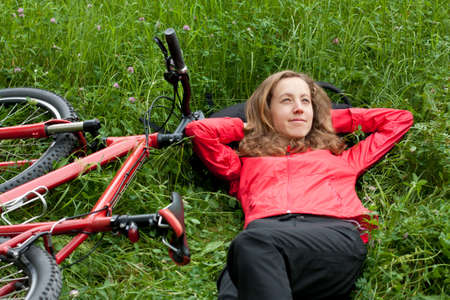 Happy woman cyclist with bike in a red tracksuit relaxes lying among of green grass on the nature. Outdoor photo