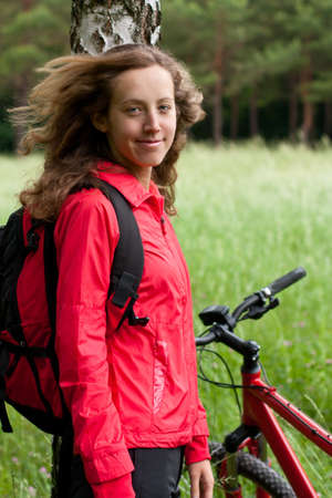 Portrait of smiling happy woman cyclist with bike and backpack in a red tracksuit against a background of green nature photo