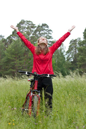 Excited happy woman cyclist standing on a nature with hands outstretched embracing vitality freedom. Outdoor photo