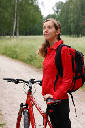 Woman cyclist with bike and backpack in a red tracksuit on a bicycle walk on the park