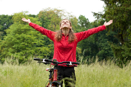 Excited happy woman cyclist standing on a nature with hands outstretched embracing vitality freedom  Outdoor photo