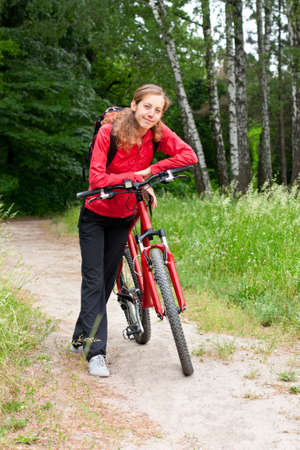 bicycle walk: Happy woman cyclist with bike and backpack in a red tracksuit on a bicycle walk on the green nature Stock Photo