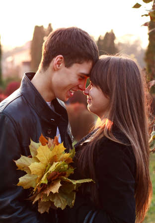 Happy smiling couple in love look at each other in autumn outdoors