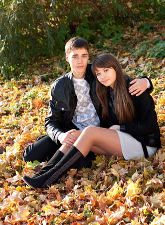Young couple in love hug sitting in autumn leaves  Outdoors photo