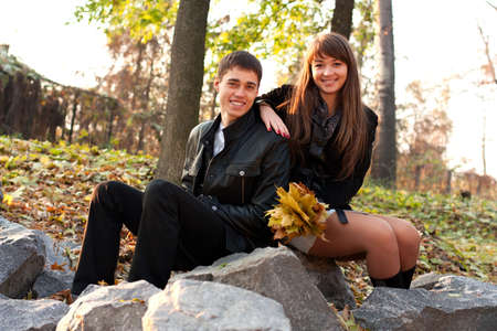 Young happy smiling couple sitting on the rocks in autumn outdoors photo