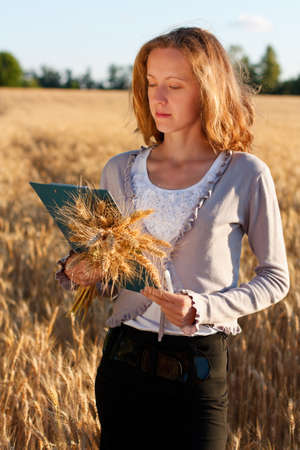 agronomist: Woman agronomist with document in hand analyzing wheat ears against a background of wheat field Stock Photo