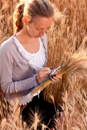 Young woman agronomist or a student with document and ears wheat in hand writes results of her experiment in the wheat field