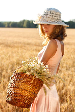Beautiful woman with basket full of ripe ears of wheat and daisies in the wheat field on a sunny day