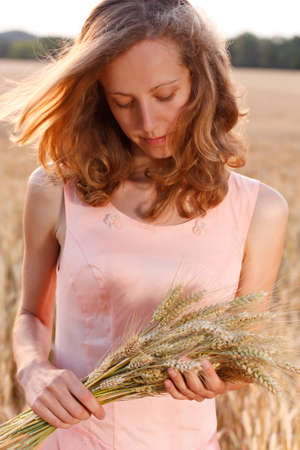 Young woman with ripe ears of wheat in the hands against the background of a wheat field in the evening photo