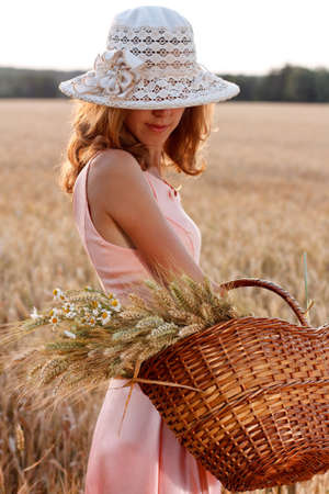 Elegante donna romantica in cappello con cesto pieno di spighe di grano mature e margherite nel campo di grano in una sera d'estate photo