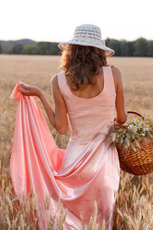 Elegant woman in a pink dress and hat with basket full of ripe wheat ears and daisies in the wheat field on a summer evening.