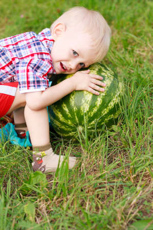 Happy child playing with watermelon outdoors in summer nature photo
