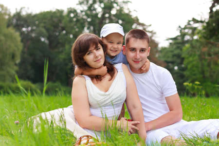 Happy family relaxing outdoor against blurred background of green nature photo