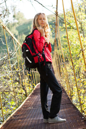 Young woman hiking in suspension bridge on a sunny bright day Stock Photo