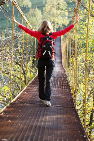 Woman hiking stand in suspension bridge with outstretched to the sides hands on a sunny nature. Position back to us