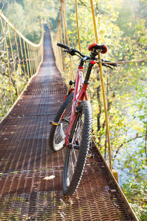 ecotourism: Red bike standing in suspension bridge against the background of nature on a sunny day