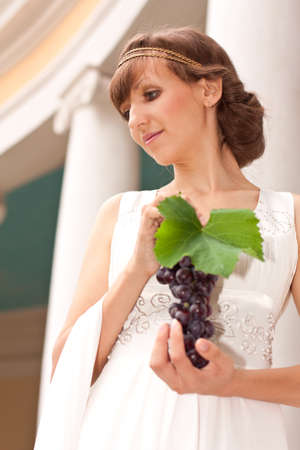 Portrait of beautiful greek woman with bunch of grapes in her hands against the background of a classical building with columns photo
